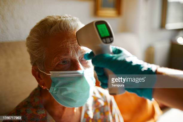 testing for temperature with an infrared thermometer. - infectious disease stock pictures, royalty-free photos & images