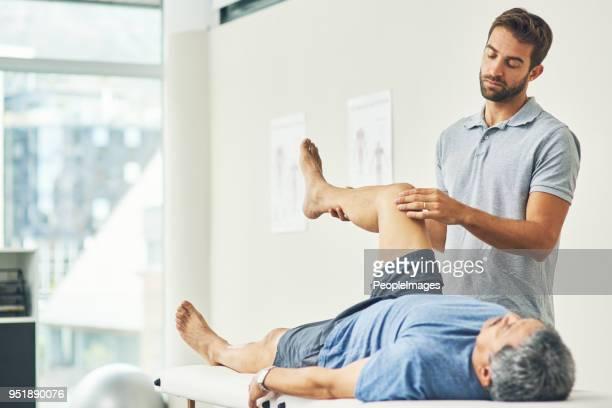 testing his mobility - coluna vertebral humana imagens e fotografias de stock