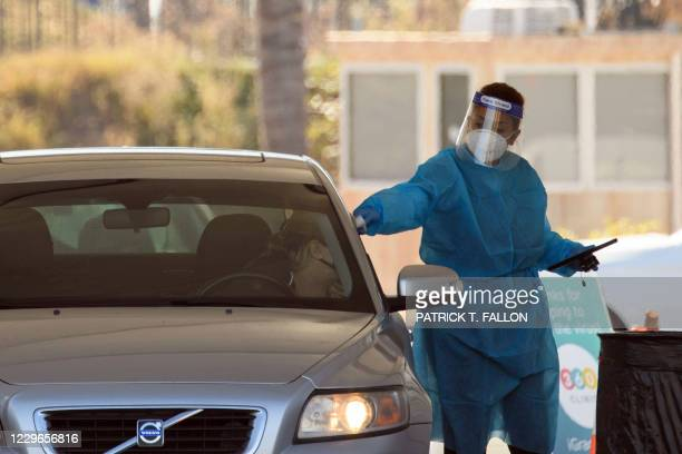 Testing site staff member conducts a temperature check at a drive-up testing site at the Orange County Fairgrounds in Costa Mesa, California,...