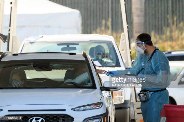 Testing site staff member uses a pulse oximeter to screen a driver at a drive-up testing site at the Orange County Fairgrounds in Costa Mesa,...