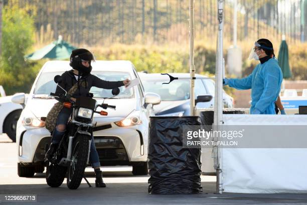 Testing site staff member uses a tool to collect paperwork from a motorcyclist at a drive-up testing site at the Orange County Fairgrounds in Costa...