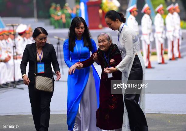 A Tet Offensive veteran is helped as she arrives to attend a ceremony marking the 50th anniversary of the military assault in Ho Chi Minh City on...