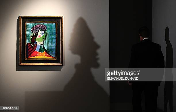 'Tete de femme' by artist Pablo Picasso is on display as a shadow of Alberto Giacometti's sculpture 'Grande tete de Diego' is projected on a wall...