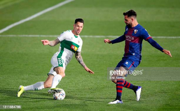 Tete Morente of Elche CF battles for possession with Pablo Insua of SD Huesca during the La Liga Santander match between SD Huesca and Elche CF at...