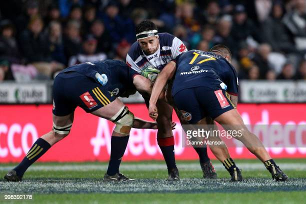 Tetera Faulkner of the Rebels is tackled by Liam Squire and Daniel LienertBrown of the Highlanders during the round 19 Super Rugby match between the...