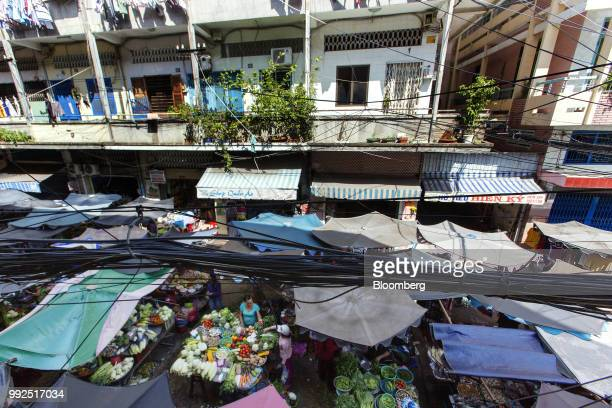 Tethered cables pass over a market covered by parasols in Ho Chi Minh City Vietnam on Wednesday June 20 2018 For decades Vietnamese have shopped...