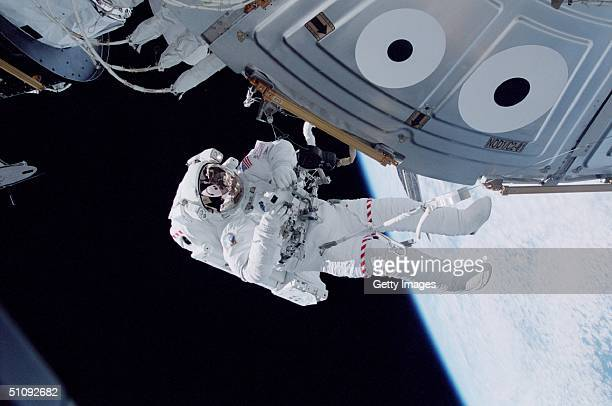 Tethered To Unity On The International Space Station Astronaut Michael LopezAlegria Prepares To Snap A Picture With A 35Mm Camera October 15 2000 A...