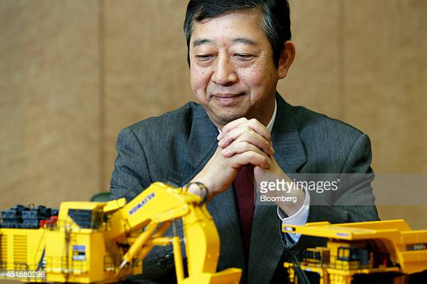 Tetsuji Ohashi president and chief executive officer of Komatsu Ltd looks at models of the company's PC8000 hydraulic excavator left and 960E dump...