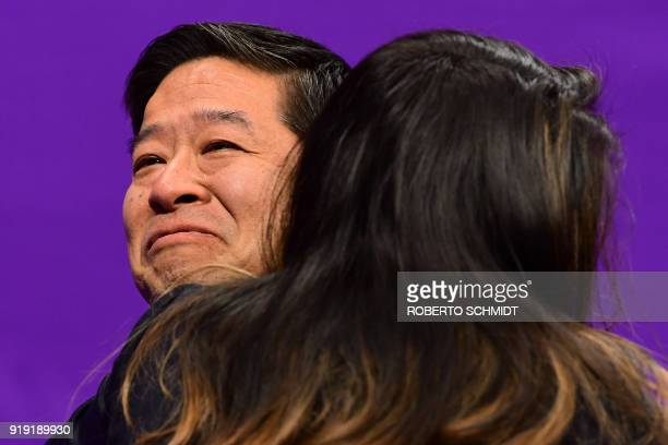 Tetsuo Abe, a member of the Japan delegation, reacts after Japan's Shoma Uno competed in the men's single skating free skating of the figure skating...