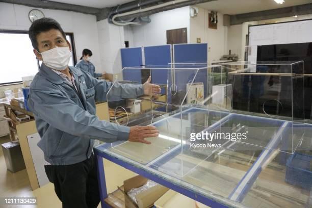 Tetsuo Taniguchi president of acrylic product maker Act in Osaka shows an aerosol box equipment aimed at shielding medical staff from aerosol...