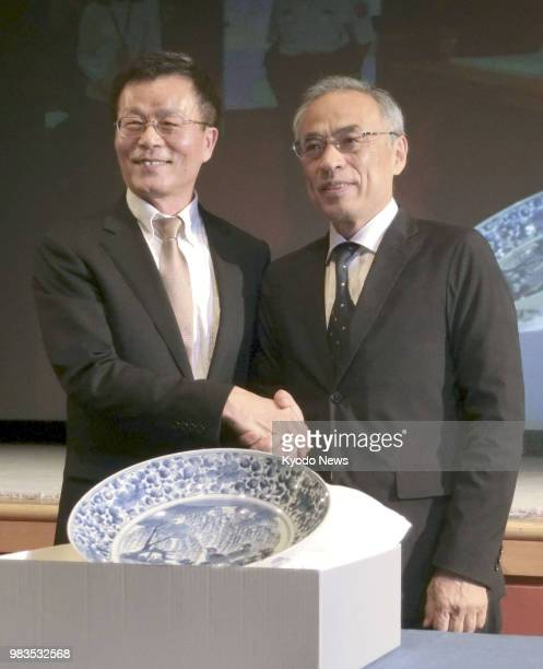 Tetsuro Degawa director of the Museum of Oriental Ceramics Osaka shakes hands with Jasper Lin director of Taiwan's National Palace Museum in Taipei...