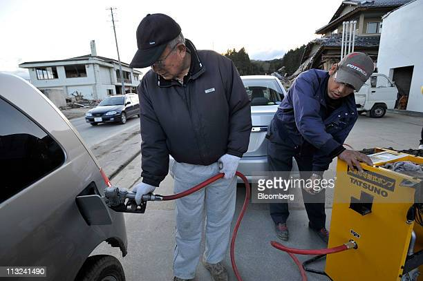Tetsuro Hosokawa left the owner of a gas station fills a customers vehicle with gasoline while worker Michito Yoshida pumps gasoline manually at his...
