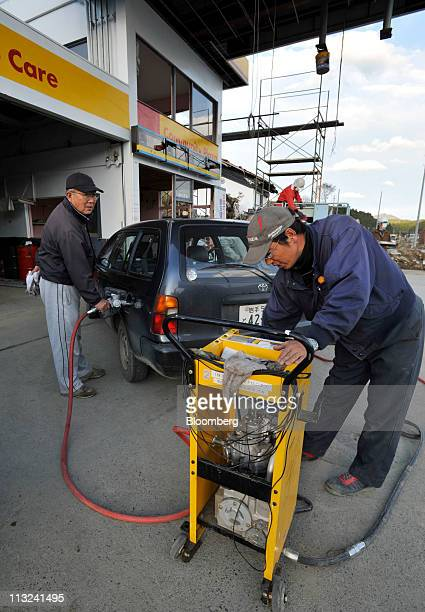 Tetsuro Hosokawa left the owner of a gas station fills a customer's vehicle with gasoline while worker Michito Yoshida pumps gasoline manually at his...