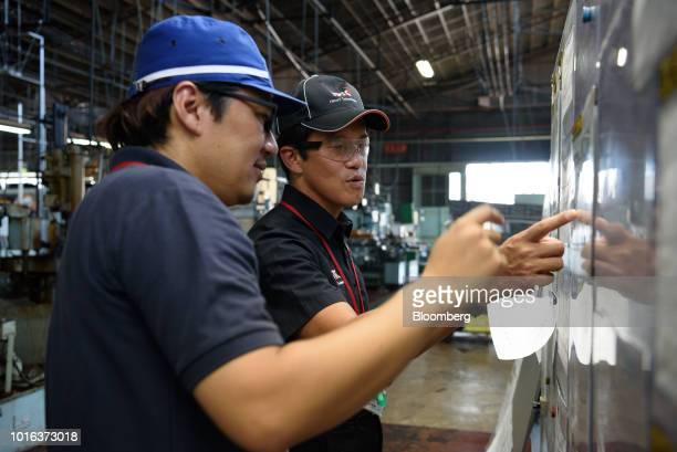 Tetsuya Kimura president of Asahi Tekko Co and iSmart Technologies Corp right speaks with an employee at an Asahi Tekko factory in Nishio Aichi...
