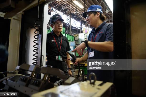 Tetsuya Kimura president of Asahi Tekko Co and iSmart Technologies Corp left speaks with an employee at an Asahi Tekko factory in Nishio Aichi...