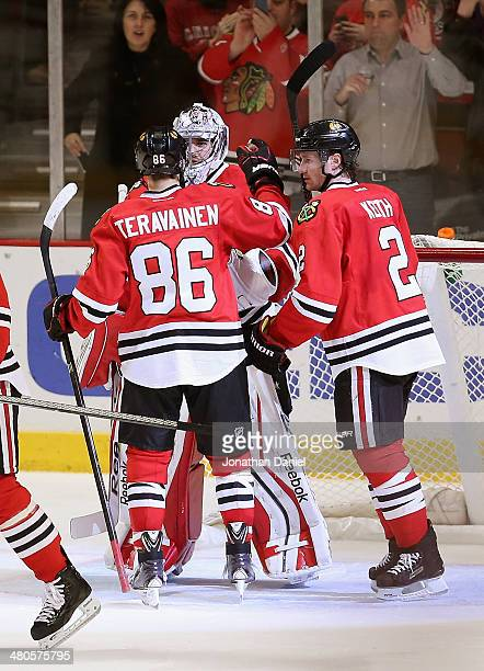 Teuvo Teravainen and Duncan Keith of the Chicago Blackhawks congratulate Corey Crawford after a win over the Dallas Stars at the United Center on...