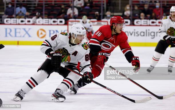 Teuvo Teravainen of the Carolina Hurricanes and Patrick Kane of the Chicago Blackhawks skate for position near the blue line during an NHL game on...