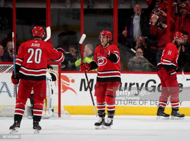 Teuvo Teravainen of the Carolina Hurricanes is congratulated by teammate Sebastian Aho after scoring a goal during an NHL game against the Boston...