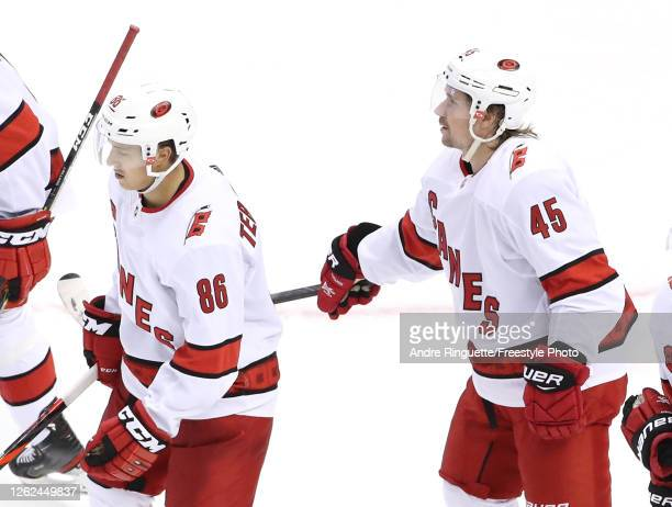 Teuvo Teravainen of the Carolina Hurricanes is congratulated by teammate Sami Vatanen after Teravainen scored a goal in the third period against the...