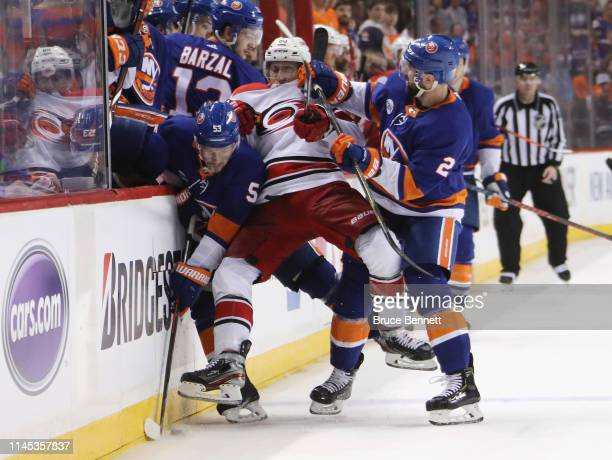 Teuvo Teravainen of the Carolina Hurricanes is sandwiched between Casey Cizikas and Nick Leddy of the New York Islanders during the third period in...