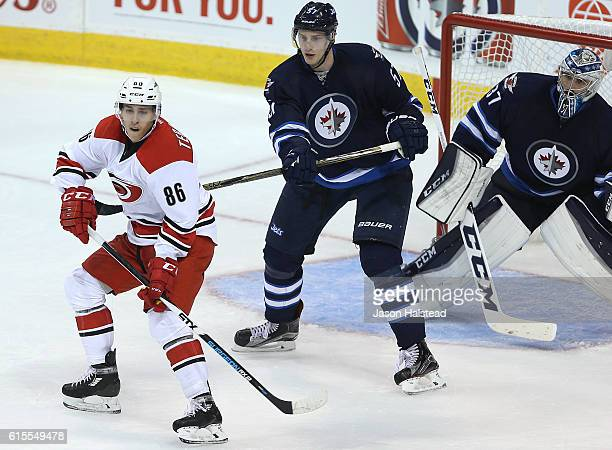 Teuvo Teravainen of the Carolina Hurricanes waits for a shot in front of Tyler Myers and Connor Hellebuyck of the Winnipeg Jets lkjljk during NHL...