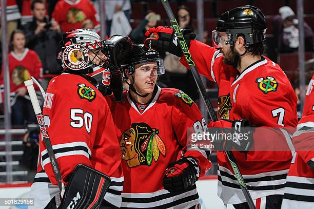Teuvo Teravainen of the Chicago Blackhawks celebrates with goalie Corey Crawford and Brent Seabrook after being named the number one player of the...