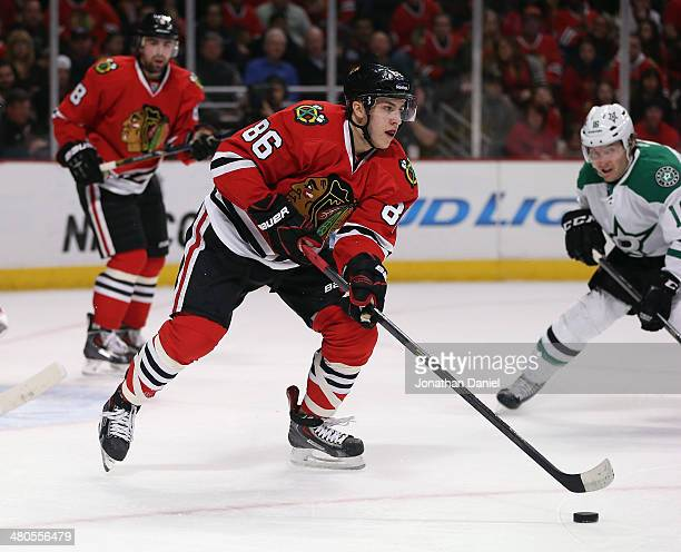 Teuvo Teravainen of the Chicago Blackhawks clears the puck out of the Blackhawks zone past Ryan Garbutt of the Dallas Stars at the United Center on...