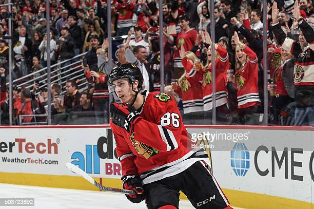 Teuvo Teravainen of the Chicago Blackhawks skates past cheering fans after scoring an empty net goal against the Pittsburgh Penguins in the third...