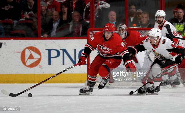 Teuvo Tervainen of the Carolina Hurricanes controls the puck away from JeanGabriel Pageau of the Ottawa Senators during an NHL game on January 30...