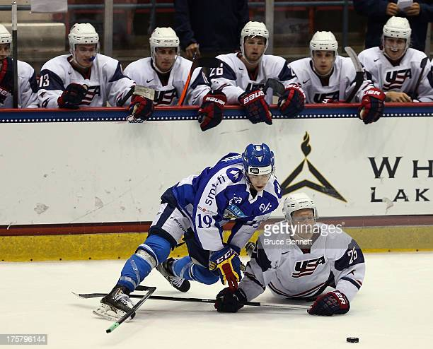 Teuvu Teravainen of Team Finland gets tangled with Henrik Samuelsson of Team USA during the 2013 USA Hockey Junior Evaluation Camp at the Lake Placid...