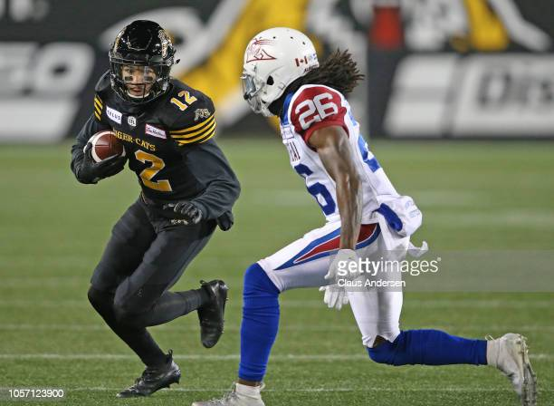 Tevaughn Campbell of the Montreal Alouettes looks to tackle Mike Jones of the Hamilton TigerCats in a CFL game at Tim Hortons Field on November 3...