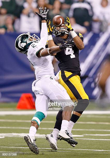 Tevaun Smith of the Iowa Hawkeyes reaches to make a catch past Darian Hicks of the Michigan State Spartans in the Big Ten Championship at Lucas Oil...