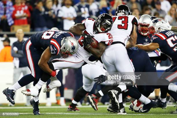 Tevin Coleman of the Atlanta Falcons is tackled by Trey Flowers of the New England Patriots during the first quarter of a game at Gillette Stadium on...