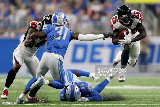 Tevin Coleman of the Atlanta Falcons runs over D.J. Hayden of the Detroit Lions and Jalen Reeves-Maybin during the second quarter at Ford Field on...
