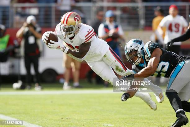 Tevin Coleman of the San Francisco 49ers dives into the end zone to score a touchdown against Eric Reid of the Carolina Panthers in the first quarter...