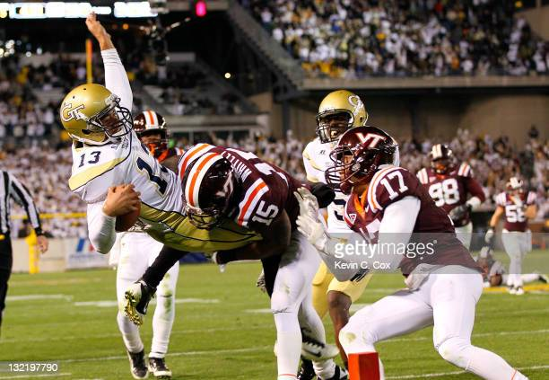 Tevin Washington of the Georgia Tech Yellow Jackets is uplifted and slammed outofbounds short of the goal line by Eddie Whitley and Kyle Fuller of...