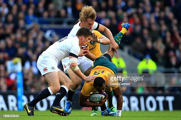 Tevita Kuridrani of Australia is tackled by Billy Twelvetrees and Owen Farrell of England during the QBE International match between England and...