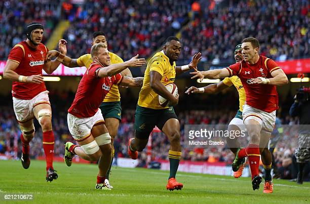 Tevita Kuridrani of Australia powers through the tackles from Ross Moriarty and George North of Wales to score his team's third try during the...