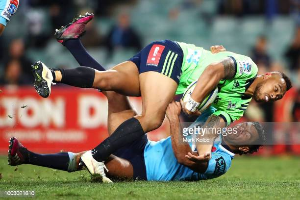 Tevita Li of the Highlanders is tackled by Kurtley Beale of the Waratahs during the Super Rugby Qualifying match between the Waratahs and the...