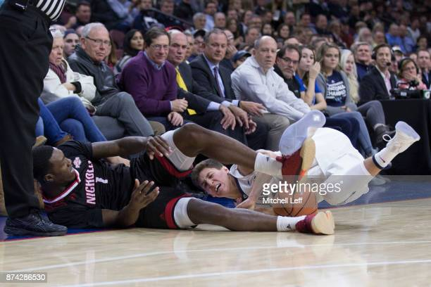 Tevon Saddler of the Nicholls State Colonels dives for the ball along with Collin Gillespie of the Villanova Wildcats in the first half at the Wells...