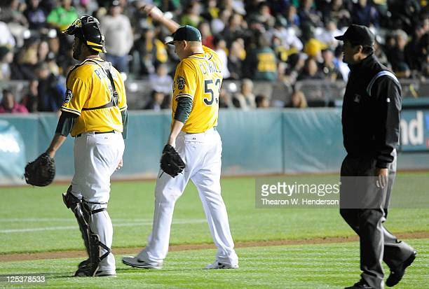 Tevor Cahill and Landon Powell of the Oakland Athletics walk to the dugout after the lights go out against the Detroit Tigers in the fourth inning...