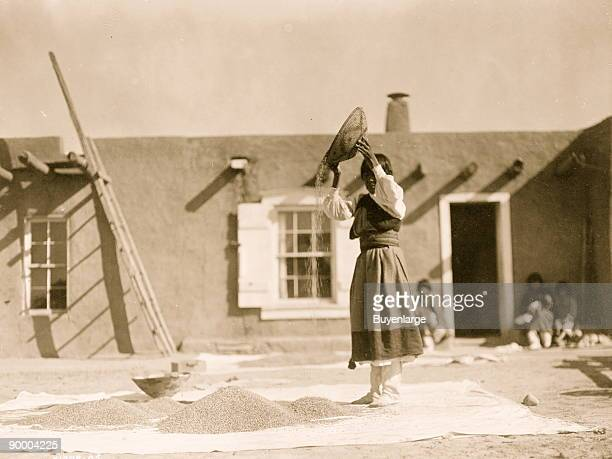 Tewa woman winnowing wheat in front of pueblo building