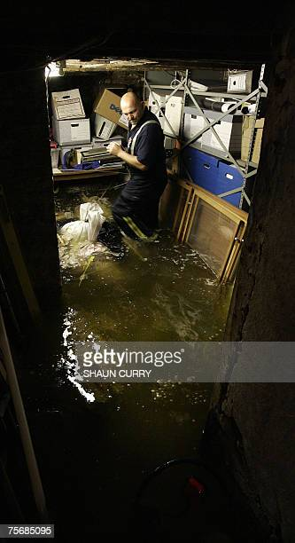 Tewkesbury, UNITED KINGDOM: A resident tries to clean up after the extensive flooding in Tewkesbury, Gloucestershire, western England, 26 July 2007....
