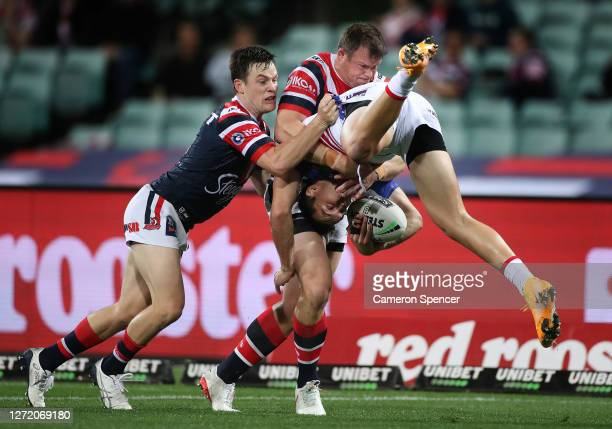 Tex Hoy of the Knights is tackled by Josh Morris of the Roosters during the round 18 NRL match between the Sydney Roosters and the Newcastle Knights...