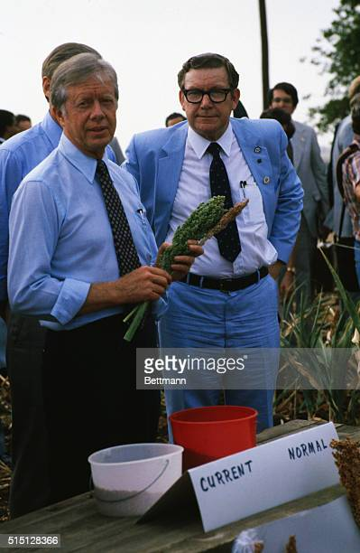 Texas Agriculture Commissioner Reagan Brown looks on as President Jimmy Carter holds milo during his tour of a drought damaged ranch   Location...