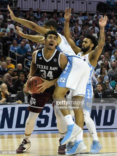 Texas AM Aggies center Tyler Davis moves past North Carolina Tar Heels forward Garrison Brooks for a score during their game in the second round of...