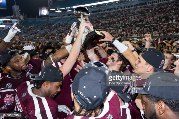 Texas AM Aggies players and family members celebrate the teams victory over the North Carolina State Wolfpack during the TaxSlayer Gator Bowl on...