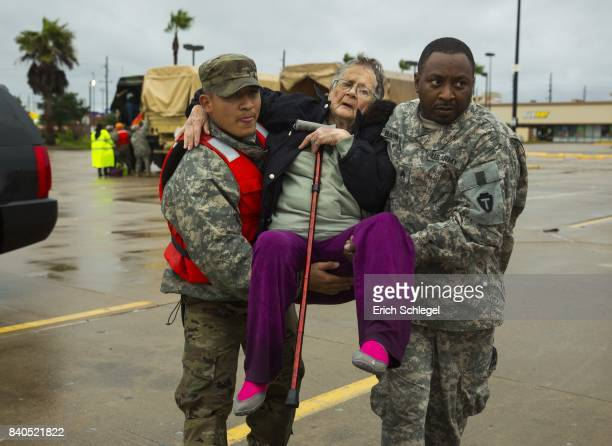 Texas Army National Guard members Sergio Esquivel left and Ernest Barmore carry 81yearold Ramona Bennett after she and other residents were rescued...