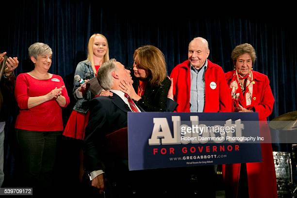 Texas Attorney General Greg Abbott gets a kiss from wife Cecilia after addressing supporters at Aldaco's Mexican Cafe after winning the Republican...