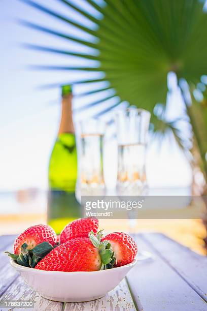 USA, Texas, Bowl of strawberries and champagne on beach with palm tree